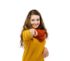 Portrait of beautiful girl in autumn clothes pointing to the camera, isolated on white background