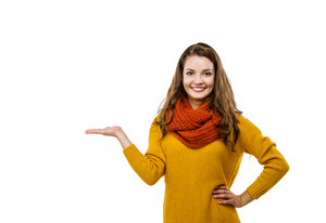Portrait of beautiful girl in autumn clothes showing a product - empty copy space on the open hand palm, isolated on white background
