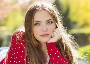 Portrait of beautiful girl in red cardigan in green prak