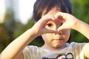 Portrait of beautiful little girl showing heart shape with her hands. Love
