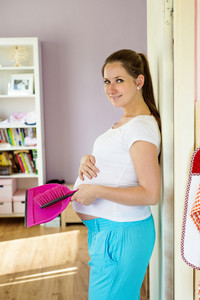 Portrait of beautiful pregnant woman holding dustpan and broom, cleaning home