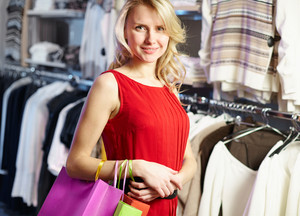 Portrait of beautiful shopper in red dress looking at camera in clothing department