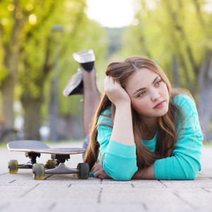 Portrait of beautiful teenage girl with skateboard lying on pavement in green alley