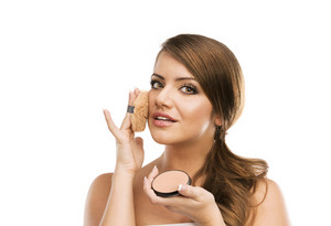 Portrait of beautiful woman putting make up on herself, isolated on white background