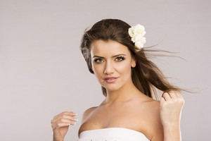 Portrait of beautiful woman with white flower in her hair. Isolate on grey background.