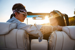 Portrait of beautiful young couple sitting in cabriolet in summer