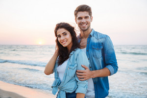 Portrait of beautiful young couple standing and smiling on the beach