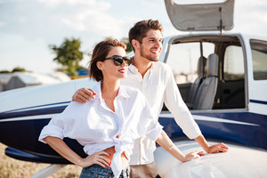 Portrait of beautiful young couple standing near small private aircraft