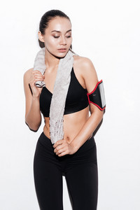Portrait of beautiful young fitness woman with armband and towel over white background