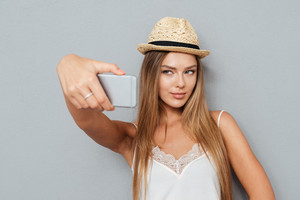 Portrait of beautiful young girl in hat making selfie with smartphone isolated on a gray background