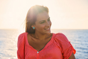 Portrait of beautiful young latina woman on holidays at sunset, sitting near sea and smiling looking away