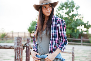 Portrait of beautiful young woman cowgirl in hat standing on ranch