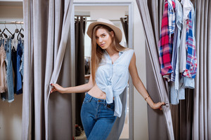 Portrait of beautiful young woman in dressing room of clothing shop