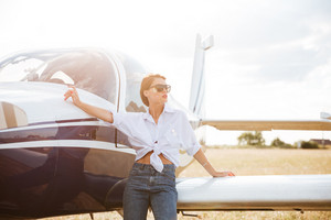 Portrait of beautiful young woman standing near private plane