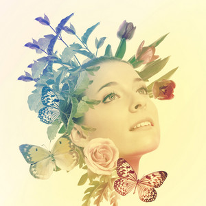 Portrait of beautiful young woman with flowers and butterflies