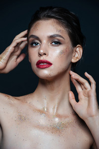 Portrait of beautiful young woman with glitter makeup over black background