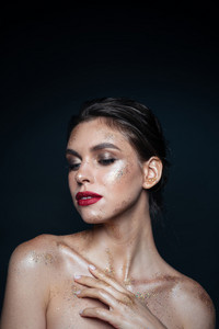 Portrait of beautiful young woman with sparkles on her face over black backgroud