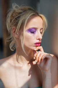 Portrait of blonde young woman with stylish purple makeup and eyes closed
