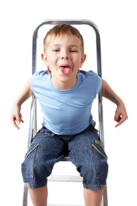 Portrait of boy in casual clothes sitting on ladder and showing tongue