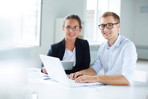 Portrait of businessman and businesswoman using laptop at meeting