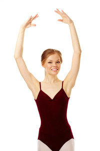 Portrait of charming ballerina with raised arms looking at camera