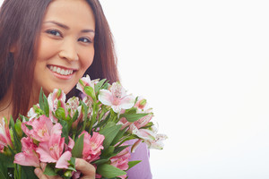 Portrait of charming female with flowers looking at camera