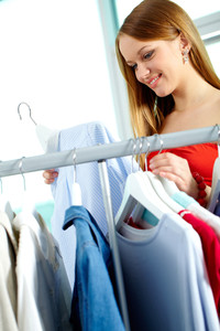 Portrait of charming girl looking at shirt in clothing department