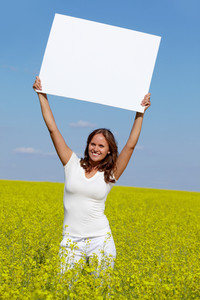 Portrait of charming girl with blank paper standing in the field