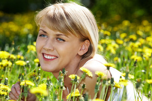 Portrait of charming girl with dandelion in green grass