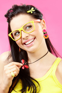 Portrait of charming woman with smile touching pendant of necklace