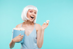 Portrait of cheerful beautiful young woman holding box of marshmallows