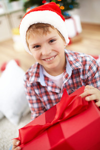 Portrait of cheerful boy with big red giftbox looking at camera on Christmas evening
