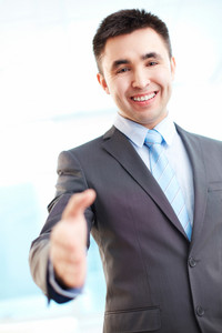 Portrait of cheerful businessman giving hand for handshake and looking at camera