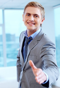 Portrait of cheerful businessman looking at camera ready for handshake