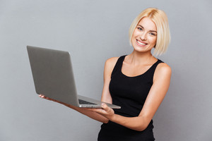 Portrait of cheerful charming young woman standing and using laptop over gray background