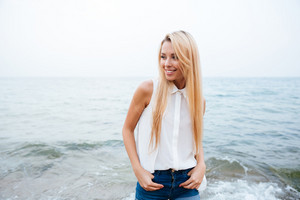 Portrait of cheerful cute young woman with long blonde hair standing on the beach