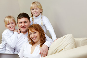 Portrait of cheerful family sitting on the sofa in the room