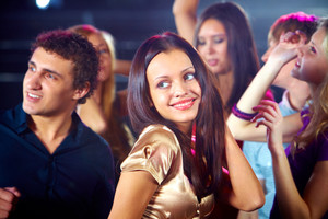 Portrait of cheerful girl dancing at party among her friends