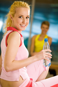 Portrait of cheerful girl holding bottle of water in hand and smiling at camera