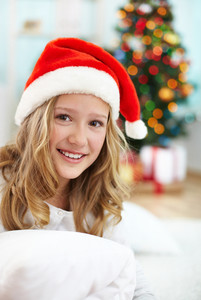 Portrait of cheerful girl in Santa cap looking at camera on Christmas evening