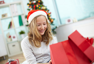 Portrait of cheerful girl looking at gift in red box on Christmas evening
