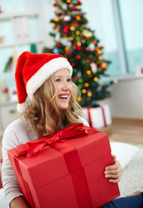 Portrait of cheerful girl with big red giftbox on Christmas evening