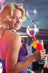 Portrait of cheerful girl with cocktail looking at camera