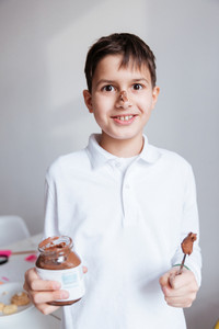Portrait of cheerful little boy eating chocolate spread from jar by spoon