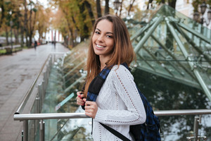 Portrait of cheerful lovely young woman with backpack in park
