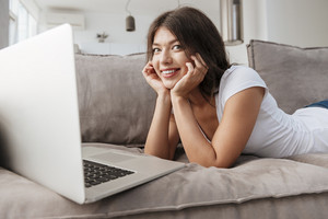Portrait of cheerful pretty young woman lying and using laptop at home