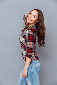 Portrait of cheerful pretty young woman standing and posing over grey background