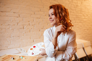 Portrait of cheerful redhead young woman painter with oil paints and palette. Look aside.