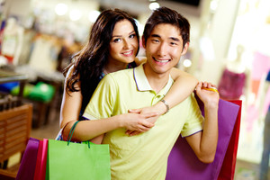 Portrait of cheerful shopping couple smiling at cam