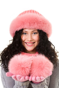 Portrait of cheerful woman in pink winter fur cap looking with smile